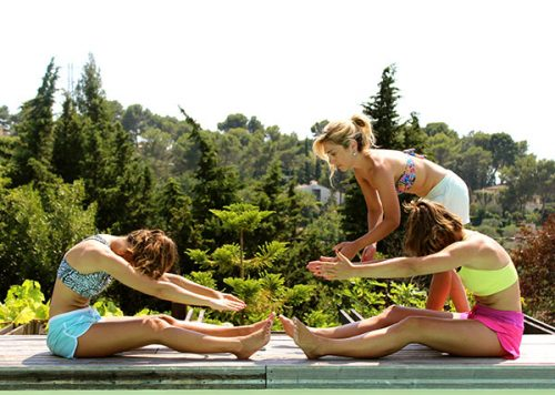 Jey, instructor of pilates, works pilates here with a group